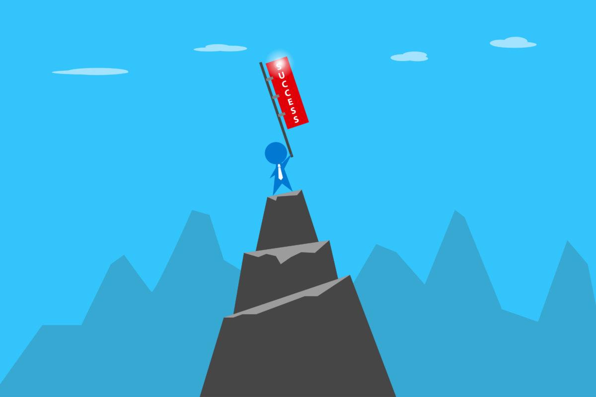ビジネスマンが山頂で成功の旗を掲げている写真