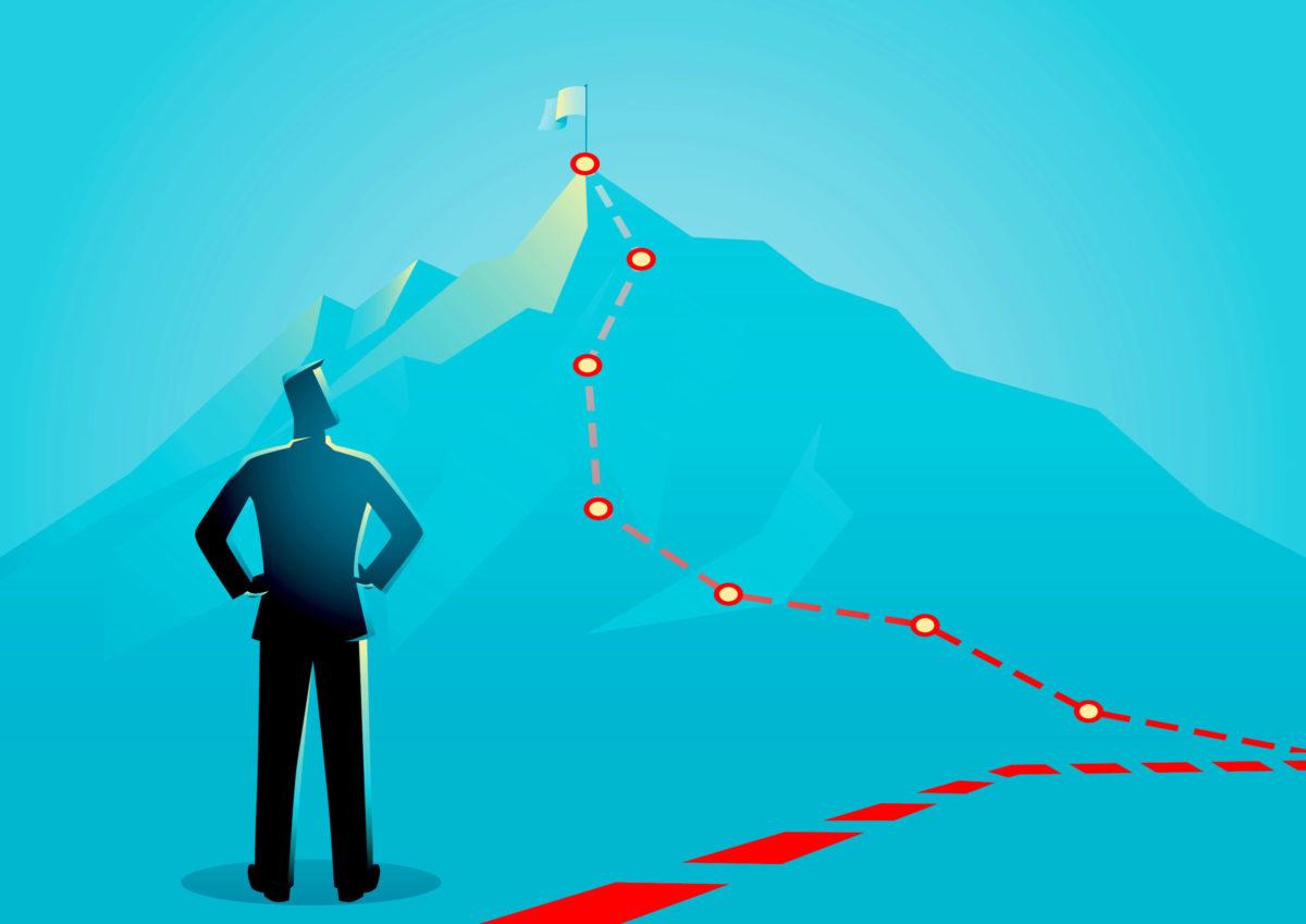 頂上までのマイルストーンを確認する男の写真