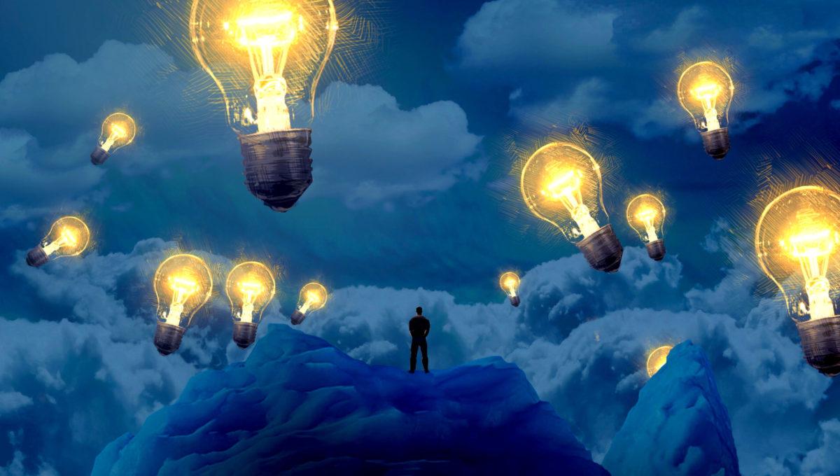 周囲で12個の電球が揺らめく岩の上で雲海を眺める男の写真