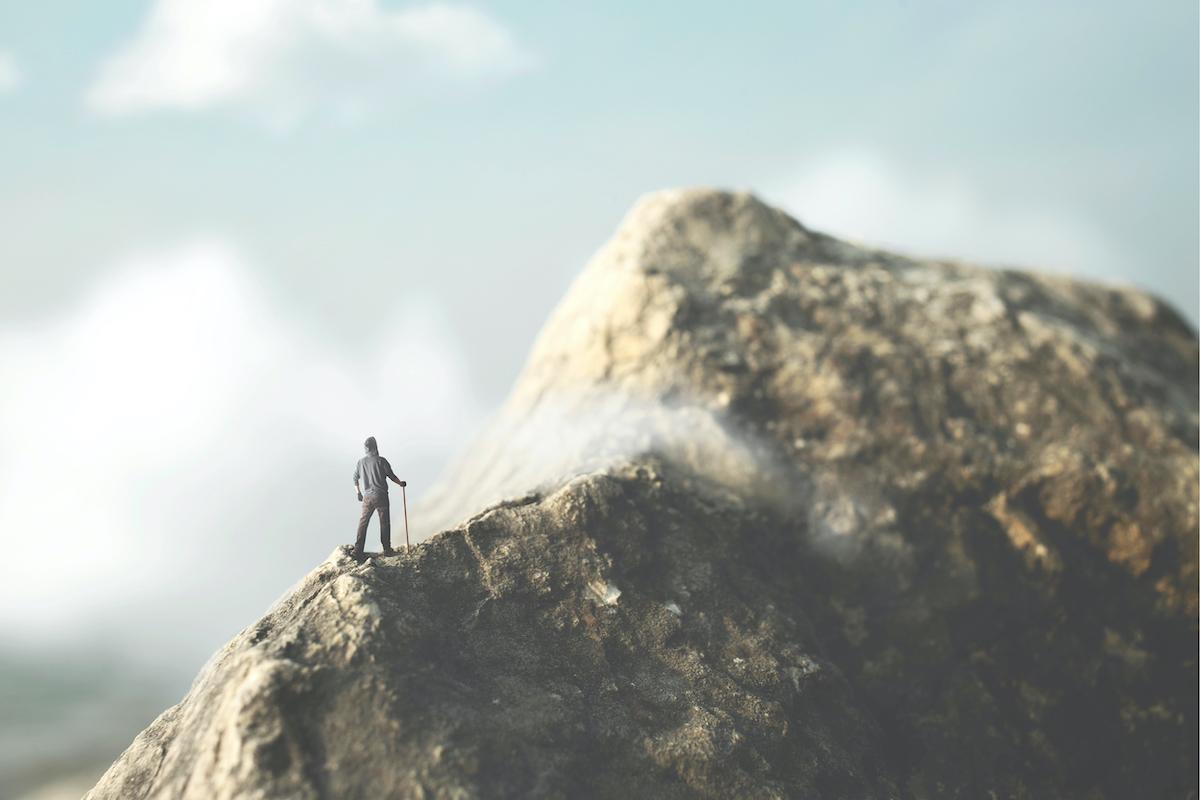頂上を目指し立ち止まる男の写真
