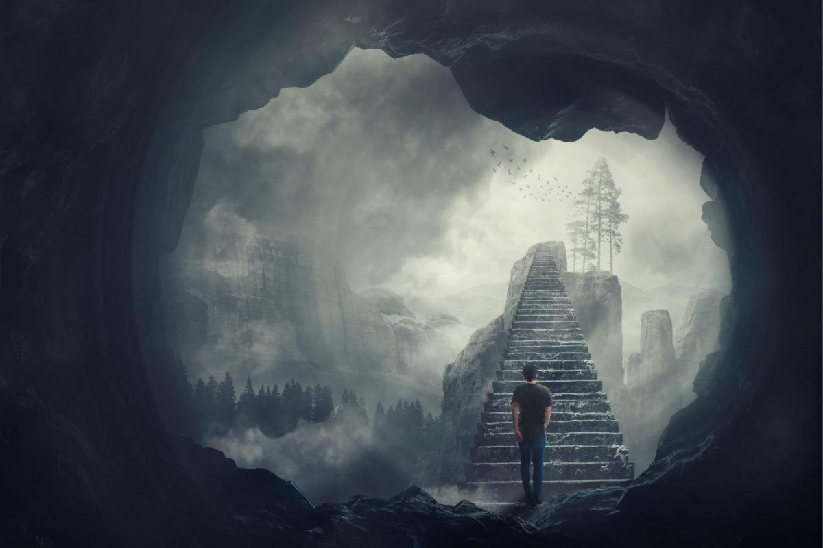 洞窟から出た先にある、先の見えない階段を登ろうとする男の写真