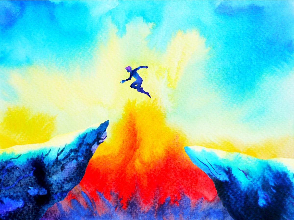 崖の先から先へ飛び移っている男の写真
