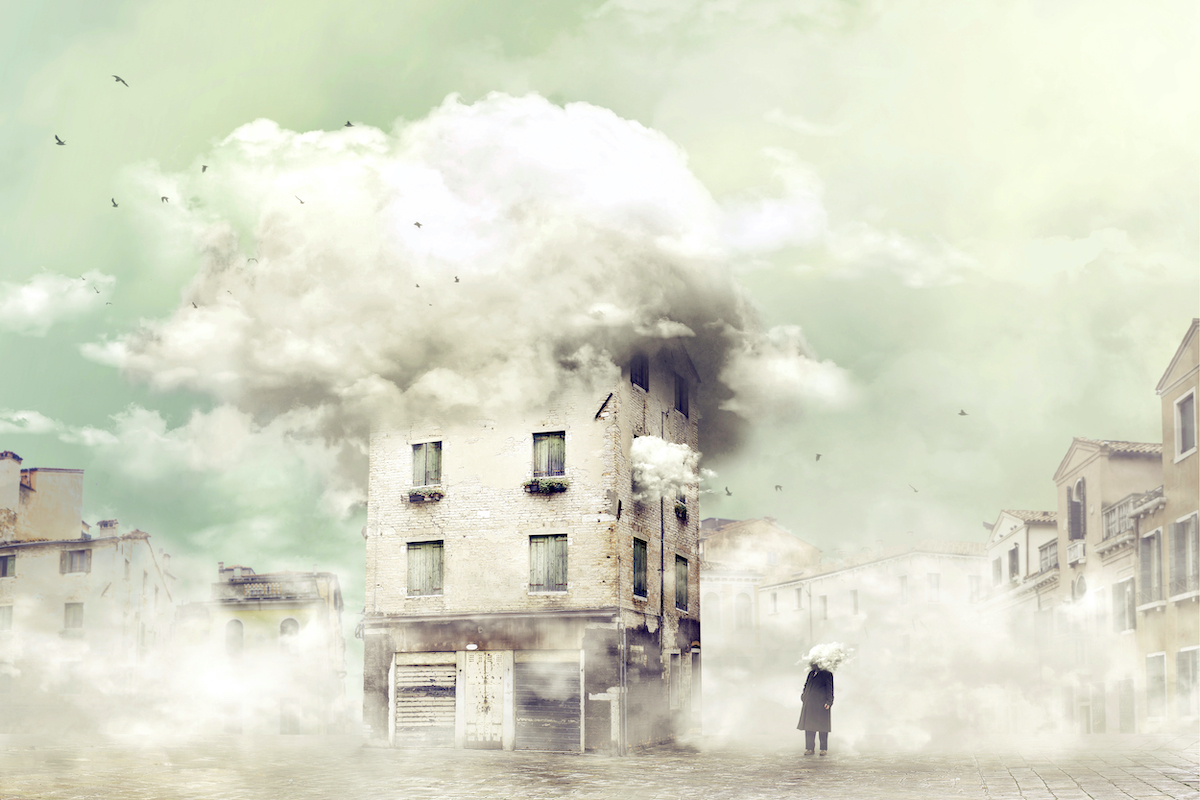 煙の出る家を茫然と見つめる男の写真
